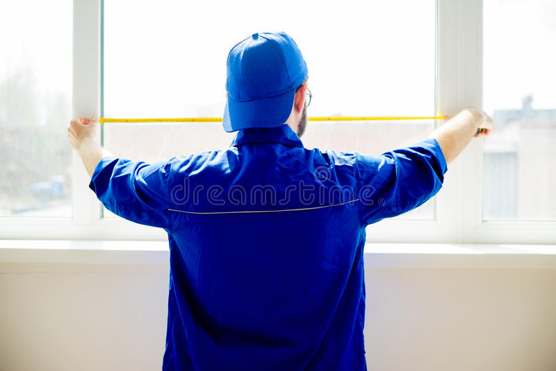 Bauarbeiter, der Fenster installiert stockfotografie