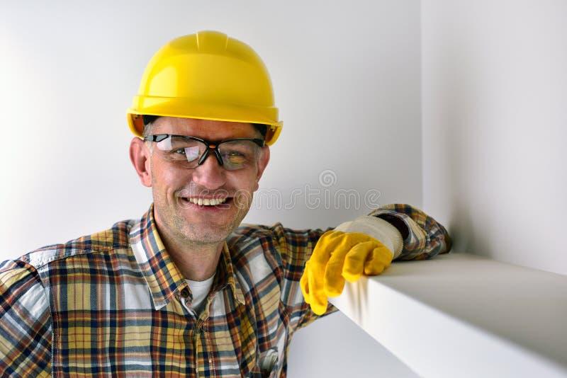 Bauarbeiter, der gelben Sturzhelm und das Lächeln trägt lizenzfreie stockfotografie