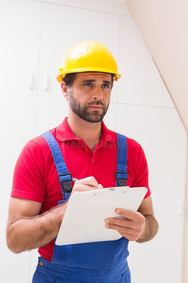Bauarbeiter, der Kenntnisse über Klemmbrett nimmt stockfotografie