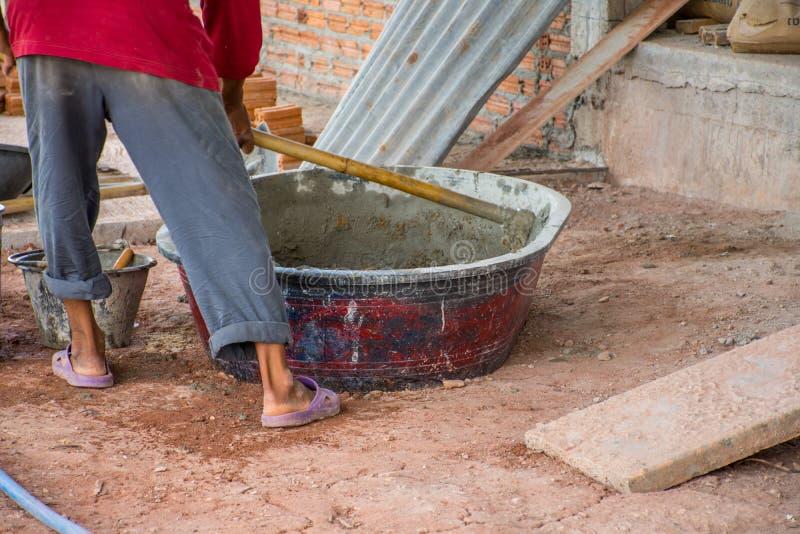 Bauarbeiter, der manuell Beton im Mischerbehälter mischt stockfotografie