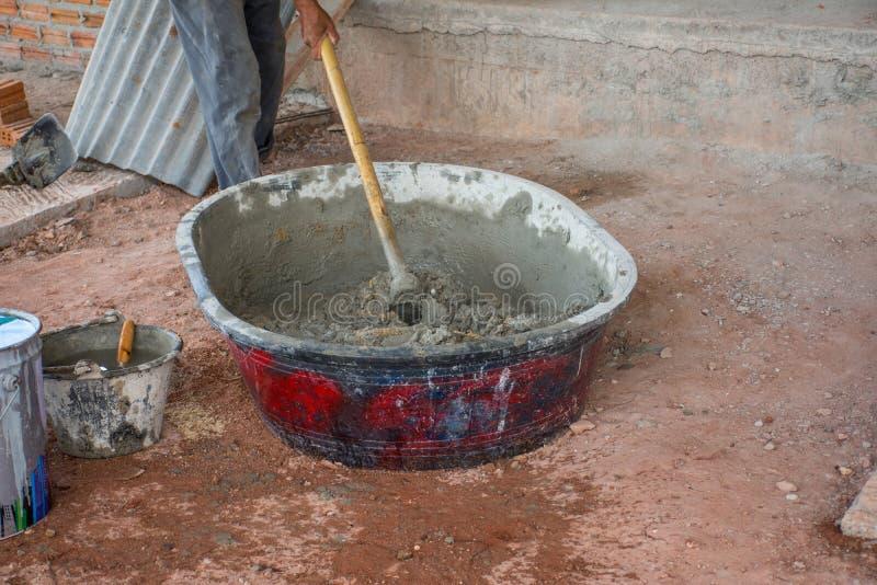 Bauarbeiter, der manuell Beton im Mischerbehälter mischt stockfotos