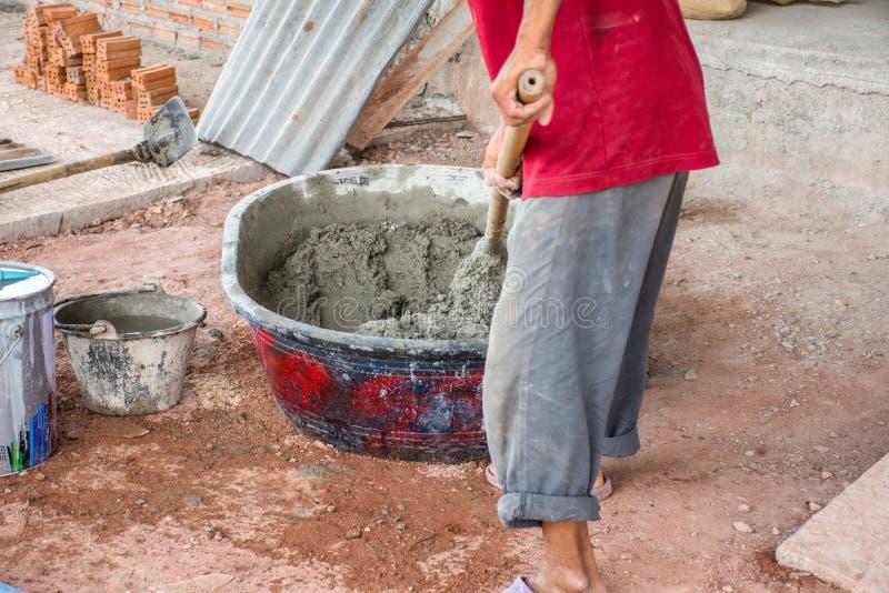 Bauarbeiter, der manuell Beton im Mischerbehälter mischt stockbild