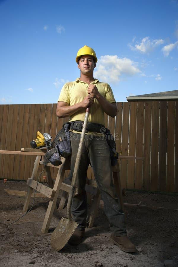 Bauarbeiter, der mit Schaufel steht stockbild