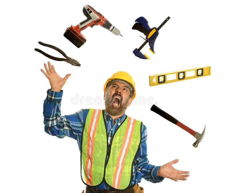 Bauarbeiter, der mit Werkzeugen jongliert lizenzfreies stockfoto