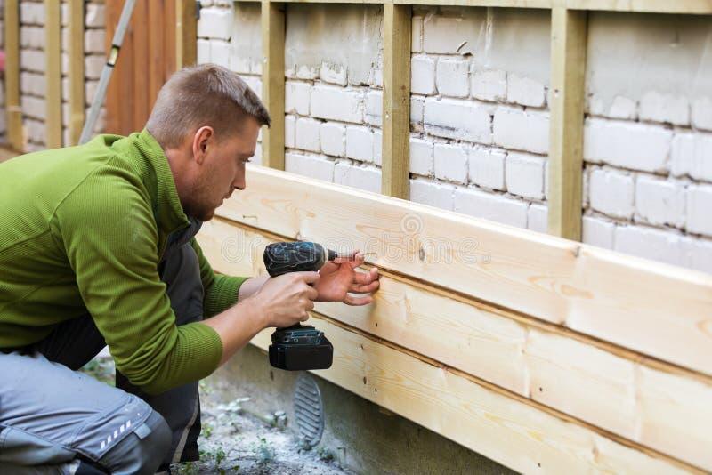 Bauarbeiter, der neue hölzerne Planken auf Hausfassade installiert stockfotos