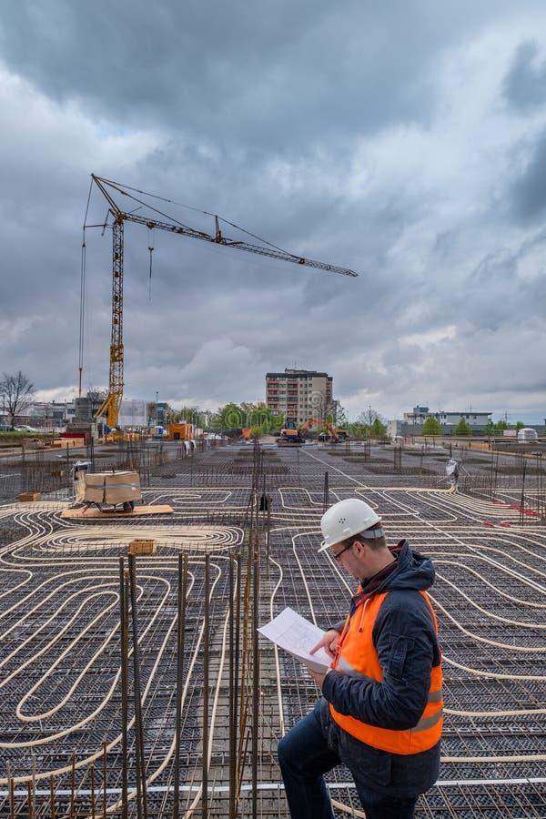 Bauarbeiter, der Pläne auf Papier hält stockbild