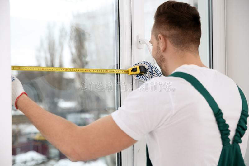 Bauarbeiter, der Plastikfenster misst Berufsinstallation lizenzfreie stockfotos