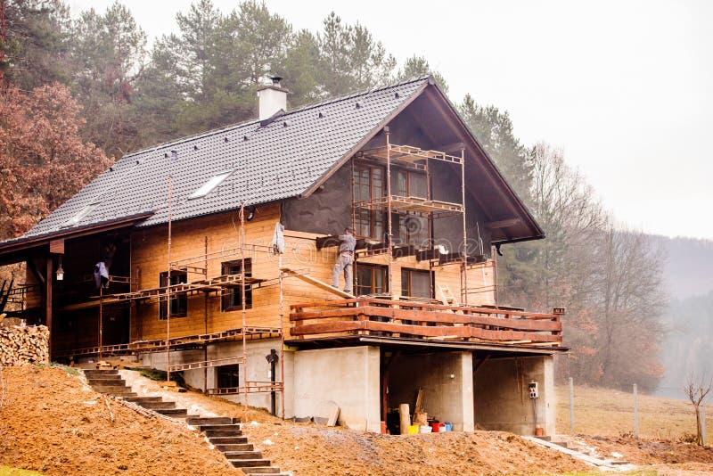 Bauarbeiter, der thermisch das Haus, hölzernes fac tuend isoliert stockfoto