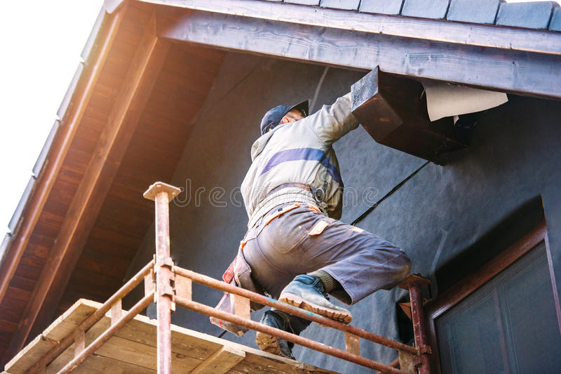 Bauarbeiter, der thermisch Haus mit Glaswolle und Folie isoliert stockfotos