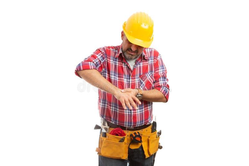 Bauarbeiter, der verletzte Hand berührt stockbilder