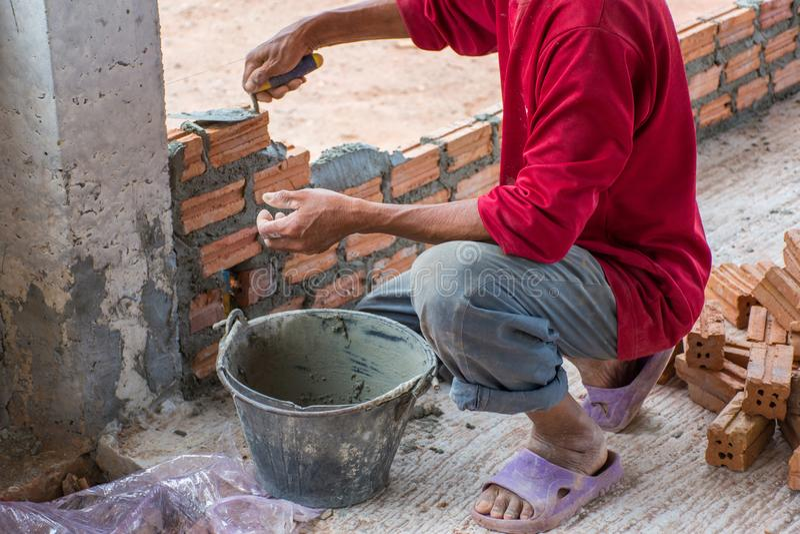 Bauarbeiter, der Ziegelsteine auf Zement für errichtendes exteri setzt stockbilder