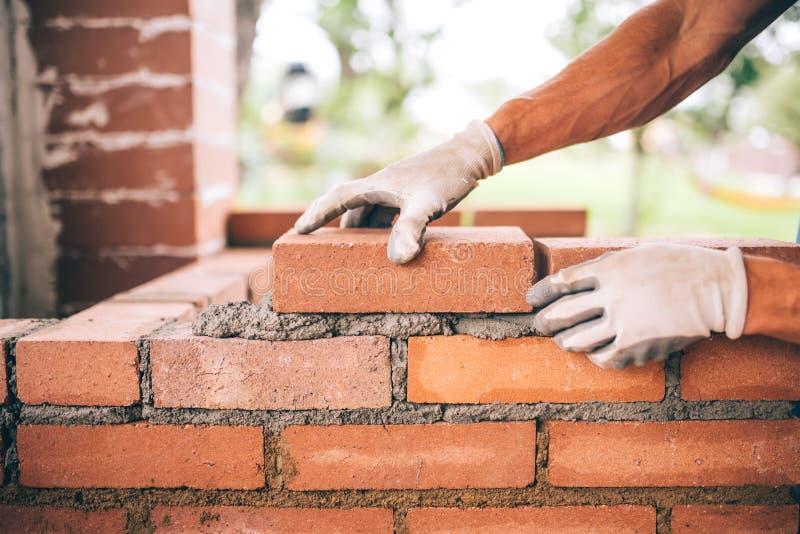Bauarbeiter, der Ziegelsteine legt und Grill im industriellen Standort errichtet Detail der Hand Ziegelsteine justierend stockbild
