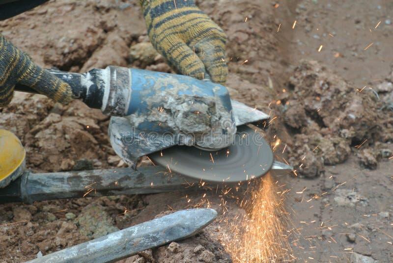 Bauarbeiter, die Bauschleifer verwenden, um Stahl an der Baustelle zu schärfen lizenzfreies stockbild