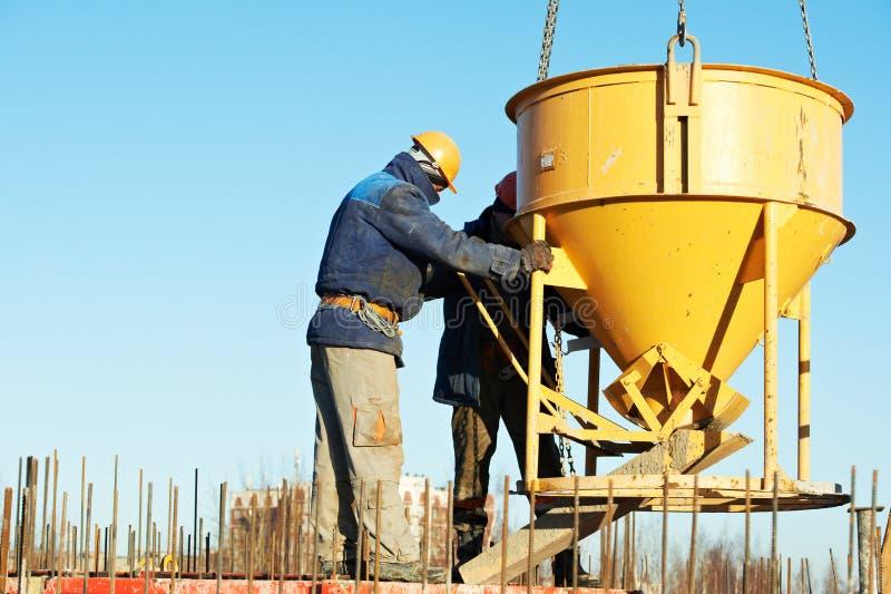 Bauarbeiter, die Beton in der Form gießen stockfotos