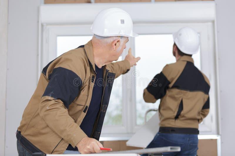 Bauarbeiter, die Fenster in Haus installieren lizenzfreie stockfotos