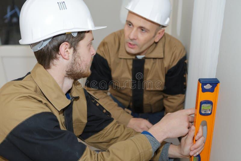 Bauarbeiter, die Plangebäude im Büro besprechen lizenzfreies stockfoto