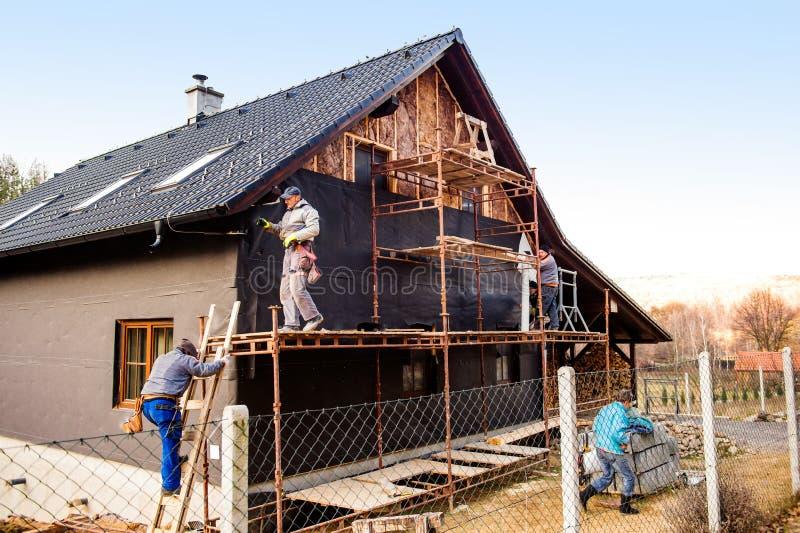 Bauarbeiter, die thermisch Haus mit Glaswolle isolieren stockbild