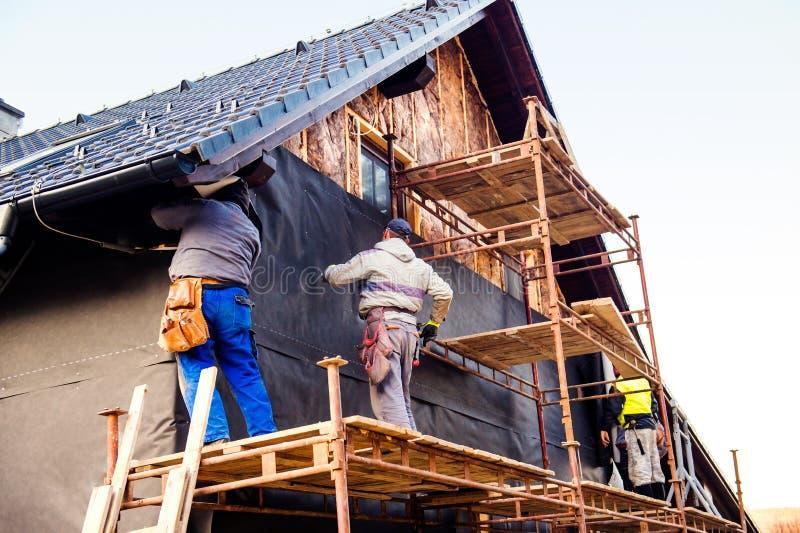 Bauarbeiter, die thermisch Haus mit Glaswolle isolieren stockbilder