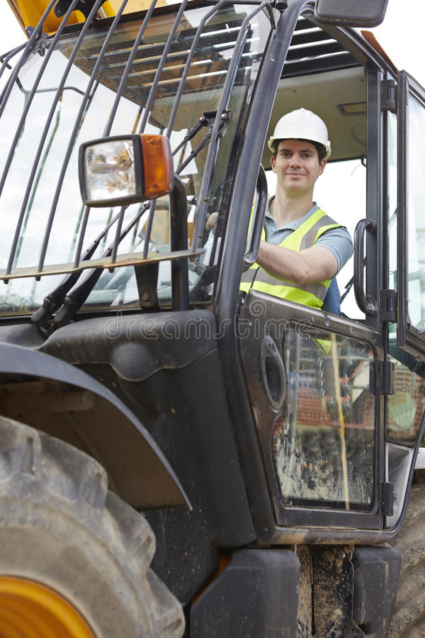 Bauarbeiter Driving Digger On Building Site stockfoto