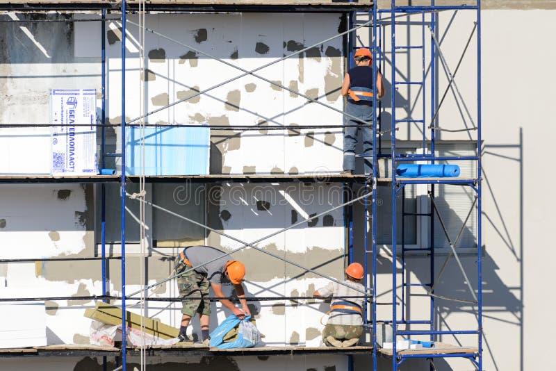 Bauarbeiter führen Arbeit über Vergipsen und Isolierungsgebäude aus stockfotografie