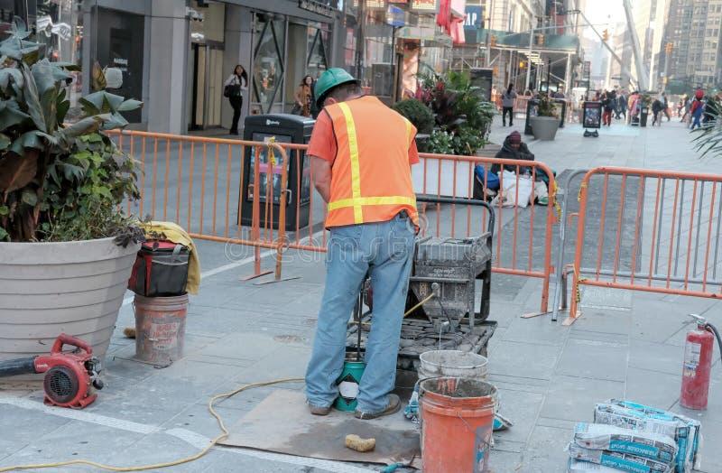 Bauarbeiter gesehene funktionierende Maschinerie im Times Square, NYC stockbilder