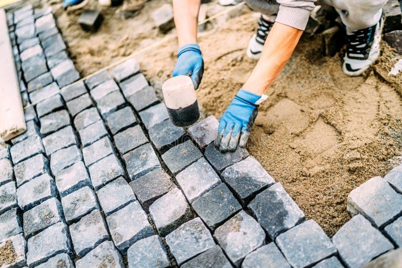 Bauarbeiter, Heimwerker, der Kopfsteingranitsteine für das Herstellen des Gehwegs verwendet Terrassen- oder Bürgersteigsdetails stockfoto