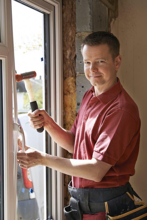 Bauarbeiter Installing New Windows im Haus stockbild