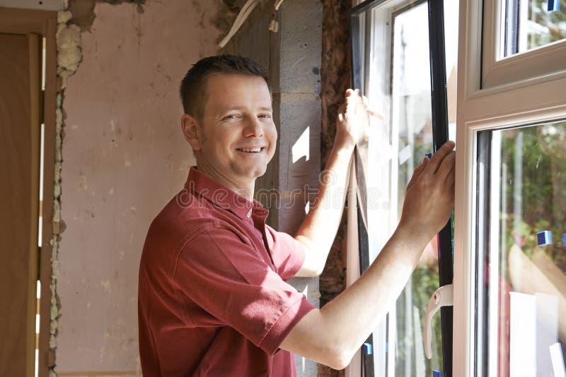 Bauarbeiter Installing New Windows im Haus lizenzfreies stockbild