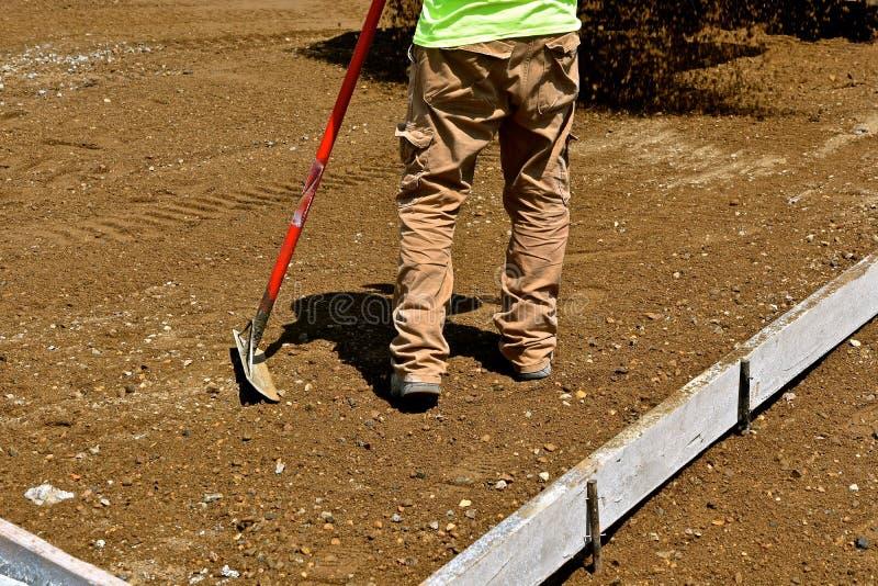 Bauarbeiter planiert Sand in einem konkreten Projekt lizenzfreie stockfotos