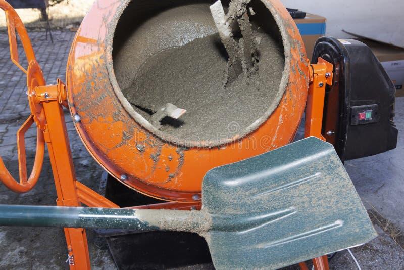 Bauarbeiter schaufelt den Sand in den Mischer Prozess des Herstellens des Zementes auf der Baustelle stockfotos