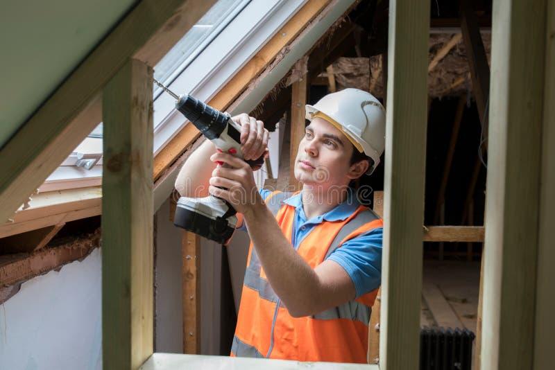 Bauarbeiter Using Drill To installieren Ersatz-Fenster stockfoto