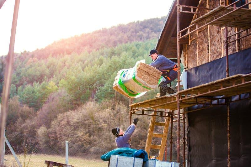 Bauarbeiter, welche thermisch die Hausfassade, stehend isolieren stockfotos