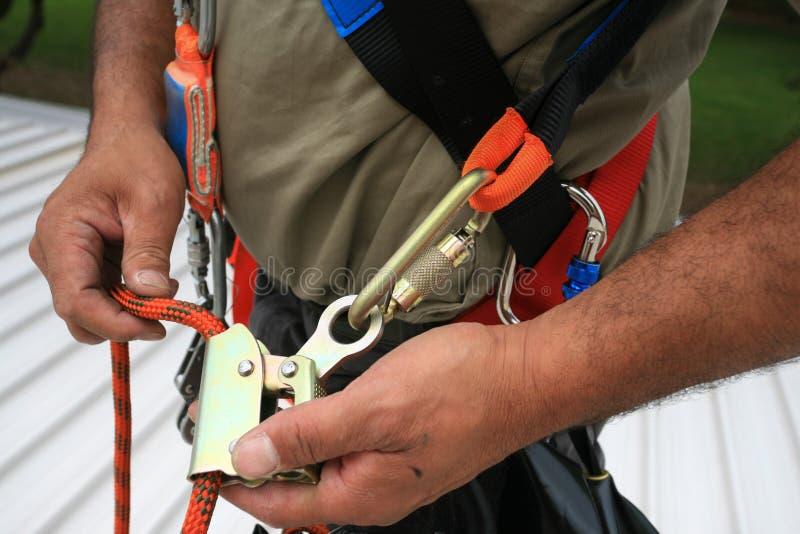 Bauarbeiterinspektions-Wartungsservices am Sicherheitsseilmist-Ausrüstungsgerät angeschlossen mit der Blockierung von Karabiner stockfotografie
