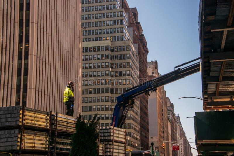 Bauarbeiterstellung auf eine konkrete Last auf einem gro?en LKW auf einer Allee in Manhattan, New York lizenzfreie stockbilder