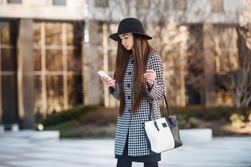 Bauatiful bedrijfsvrouw gebruikend smartphone en lopend dichtbij de bureaubouw op de straat royalty-vrije stock afbeelding