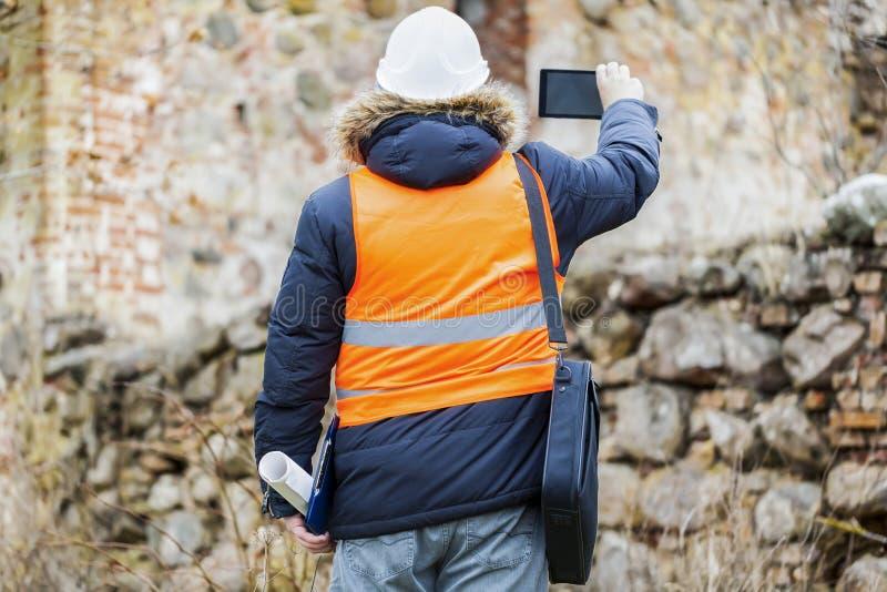Bauaufsichtsbeamte mit Tablet-PC an den alten Ruinen stockfotografie