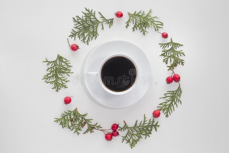 bauble błękitny bożych narodzeń składu szkło Filiżanka kawy z zielonymi tuj gałązkami i czerwonymi dzikimi różanymi owoc na biały fotografia royalty free