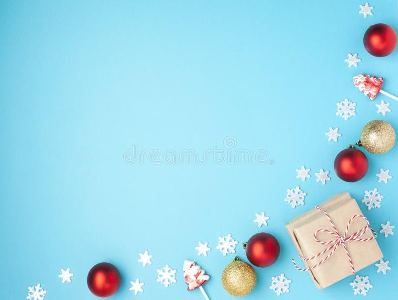 bauble błękitny bożych narodzeń składu szkło Rama od czerwonych piłek, prezenta, lizaków i płatek śniegu na pastelowym błękitnym  obrazy stock