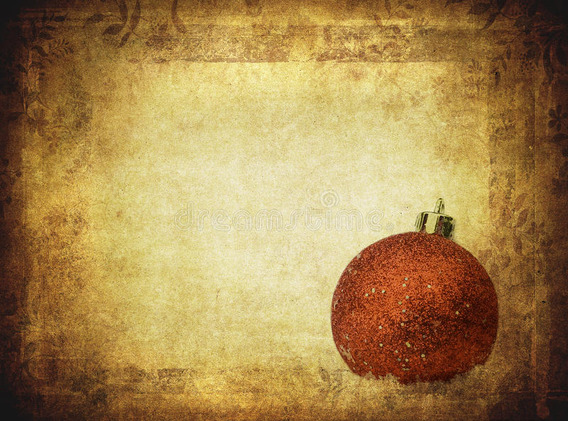 Bauble over vintage paper, christmas background royalty free stock image