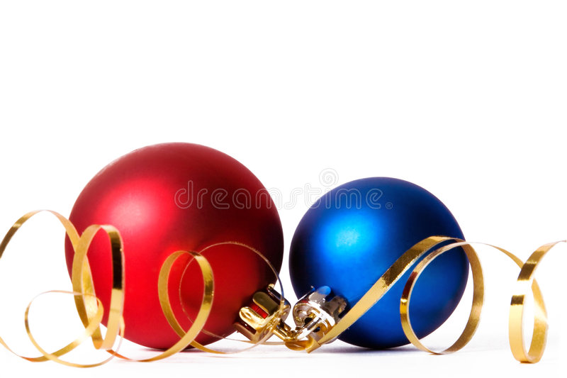 Two Christmas baubles with gold ribbon spirals stock image