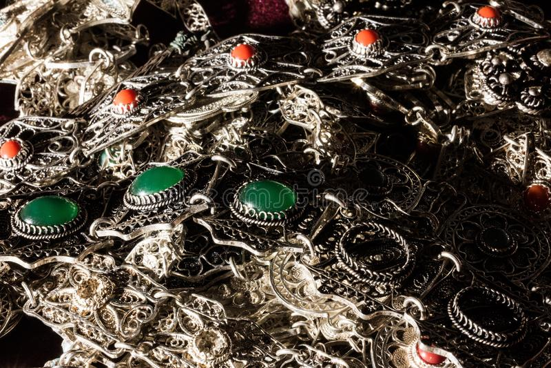 Bauch des silbernen Schmucks mit den grünen und roten Edelsteinen lizenzfreie stockfotos
