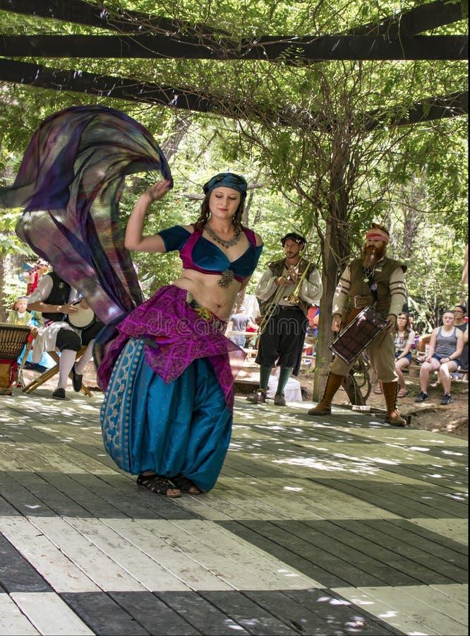 Bauchtänzerin in der Bewegung mit kostümierten Musikern in der Rebe bedeckte Nische an Renassiance-Festival im Muskogee Oklahoma  lizenzfreie stockbilder