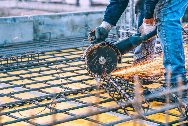 Baudetails mit der Arbeitskraft, die Stahlstangen und Bewehrungsstahl mit Winkelschleifer schneidet Gefiltertes Bild lizenzfreie stockbilder