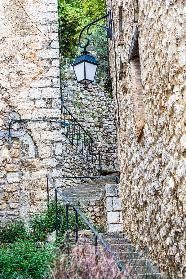 Bauduen, France - June 18, 2018. Stairs with lantern in tiny picturesque French street with traditional stone houses stock images