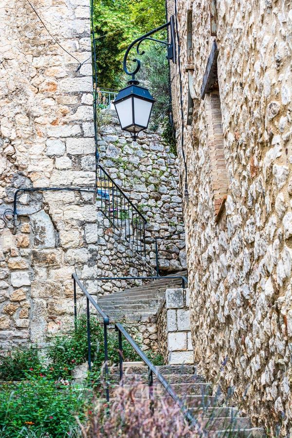 Bauduen, Francia - 18 de junio de 2018 Escaleras con la linterna en calle francesa pintoresca min?scula con las casas de piedra t imagenes de archivo
