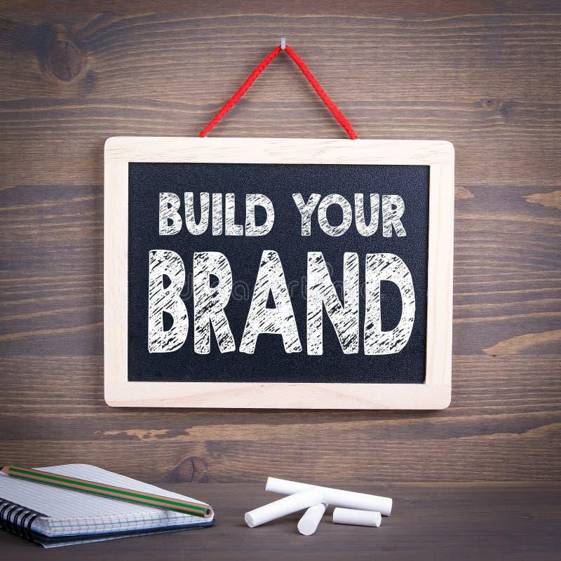 Bauen Sie Ihr Markenkonzept auf Tafel auf einem hölzernen Hintergrund lizenzfreies stockbild