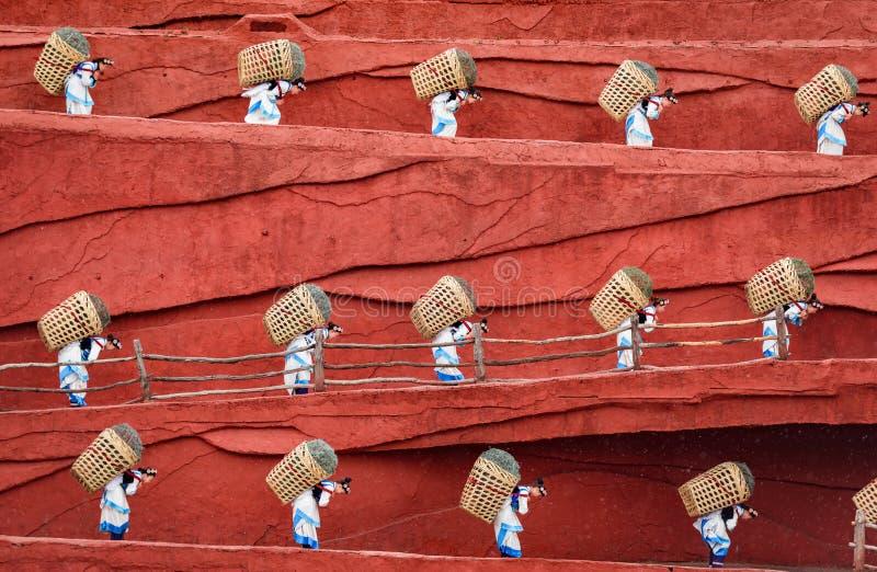 Bauern, die Körbe auf der Rückseite tragen, Lijiang, Yunnan, China stockfoto