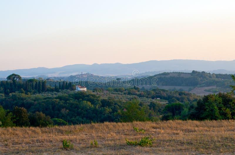 Bauernhaus in der toskanischen Landschaft mit altem Dörfchen lizenzfreie stockfotografie