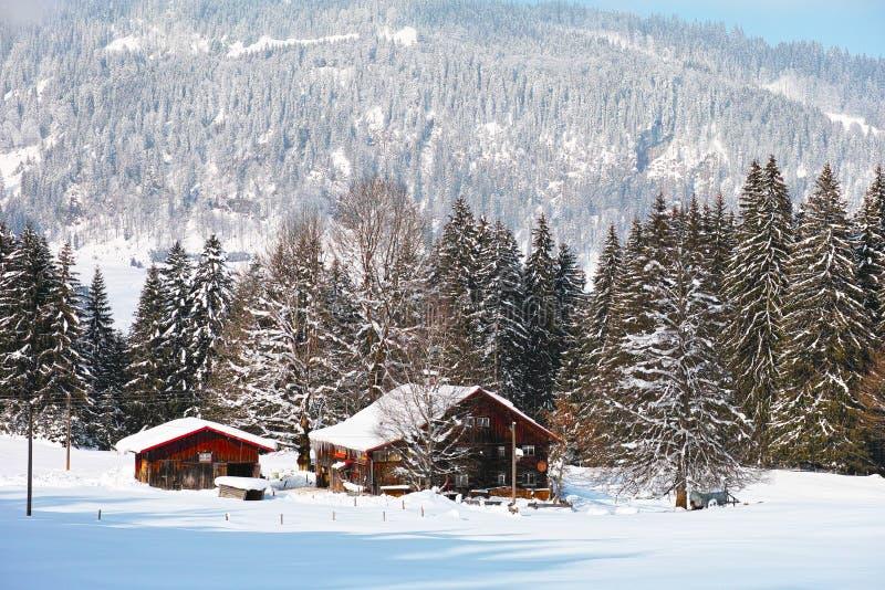 Bauernhof in der alpinen Landschaft schneebedeckt stockbilder