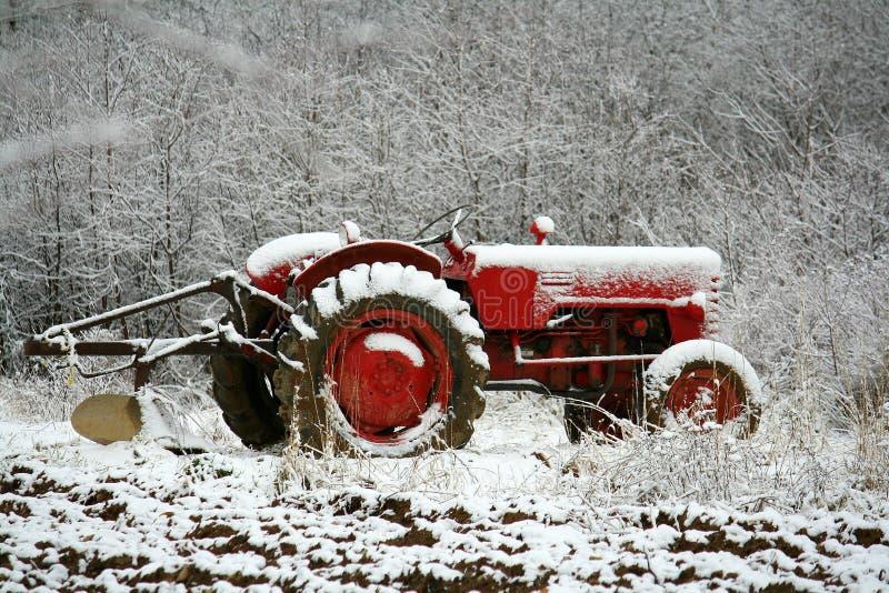 Bauernhof-Traktor im frühen Schnee stockbild